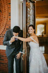 Hand kisses around the door before the wedding