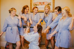 Bride chugs wine while bridesmaids look on