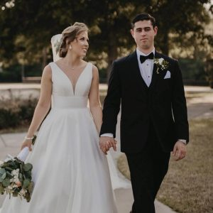 Groom and Bride walk hand in hand outside