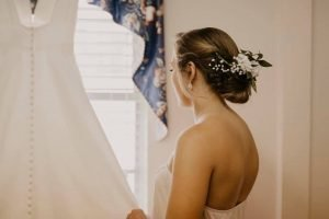 Bride with her hair done staring at her dress