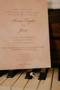 Invitation and wedding ring on the piano