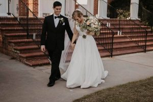 Bride and Groom walking outside the church