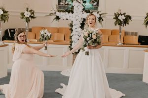 Bridesmaid kneeling in front of the bride