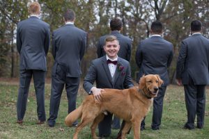 Groom with the family dog and honorary groomsman