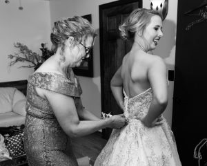 Mother zips up the bride's dress